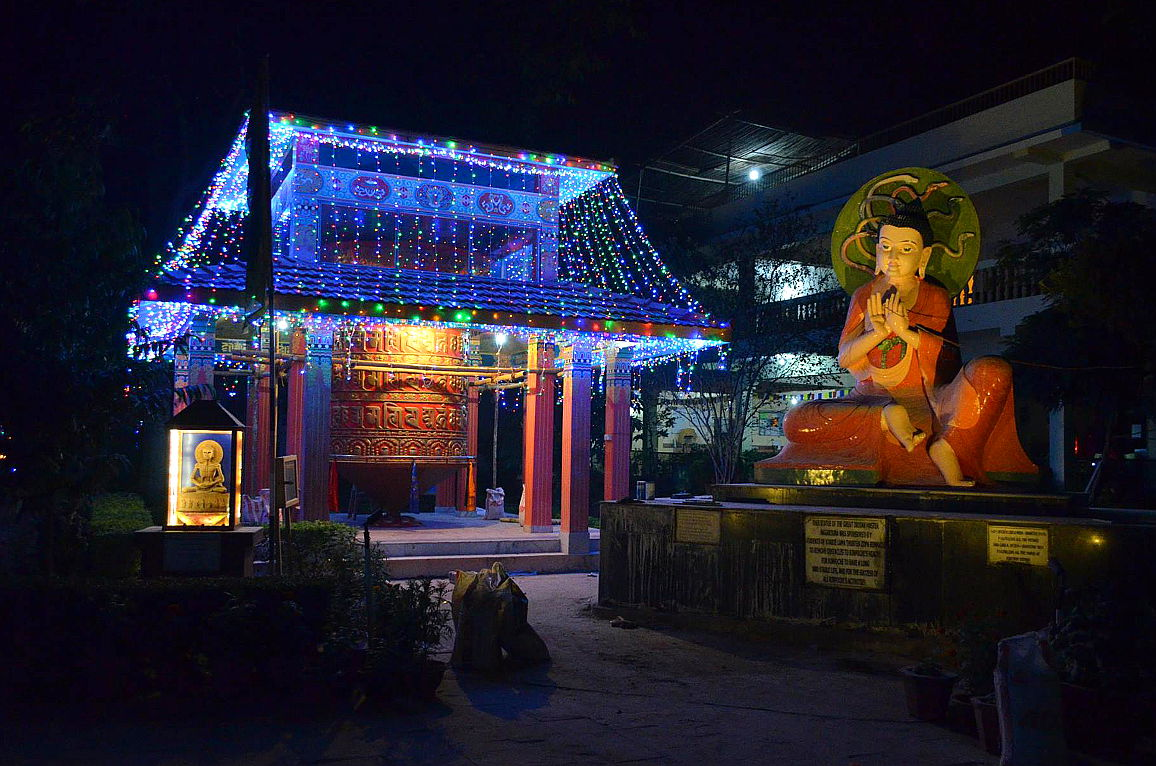 Prayer wheel and Nagarjuna statue illuminated