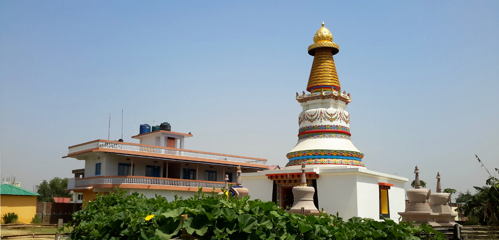 The view near the entrance with accommodation block, and shrine room topped by the Kadampa Stupa surrounded by eight smaller stupas