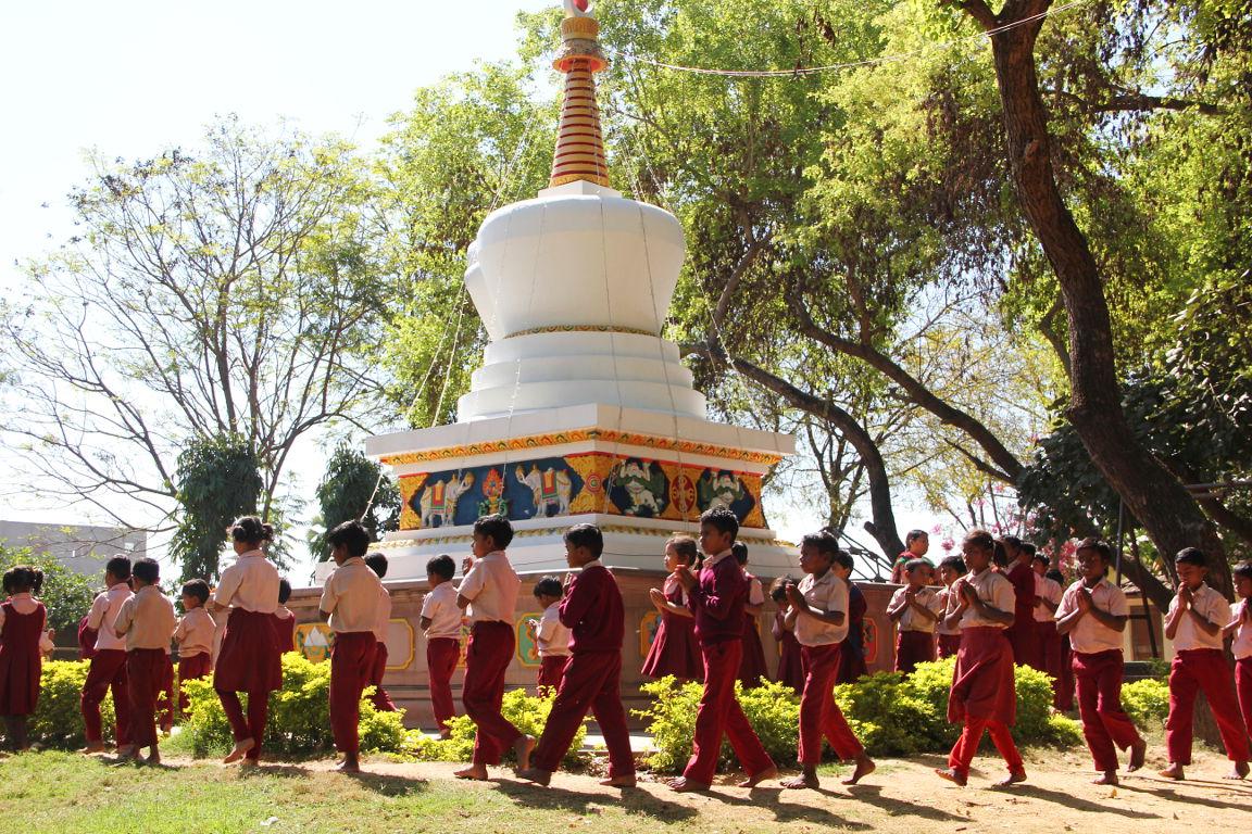 Students circumambulating the long-life stupa in the grounds of Maitreya School