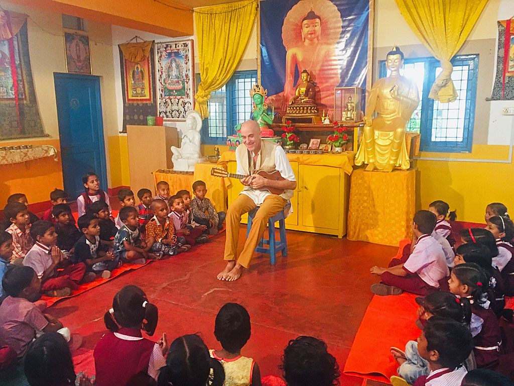 A visiting musician entertaining the children with music