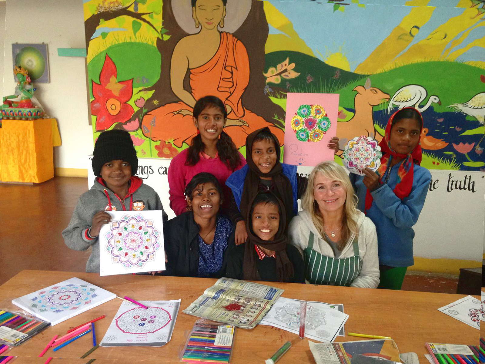 Children, all smiles, with a volunteer art therapist