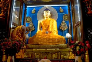 Offering of robes to the Lord Buddha statue in the Mahabodhi shrine room