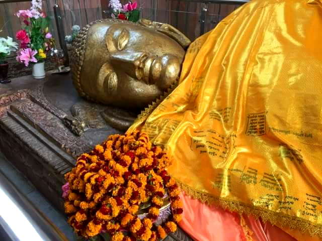 At Kushinagar inside the Mahaparanirvana Temple marking where Lord Buddha passed away, robes are offered to the holy body