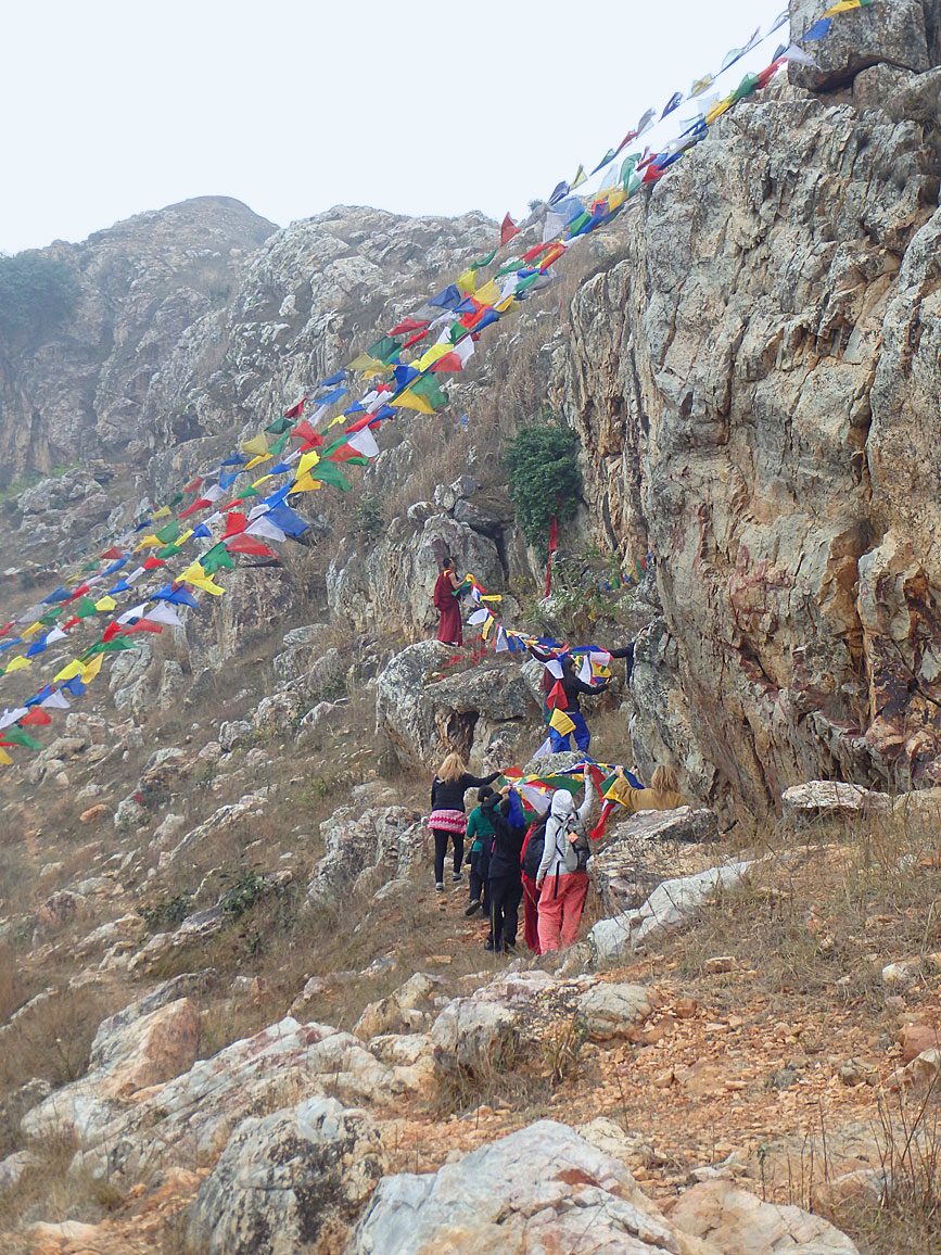 Students hanging prayer flags on the mountain above the Mahakala Cave, not far from Bodhgaya