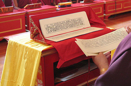 Reading prayers from a traditional Tibetan pecha